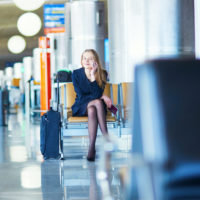 Young woman in international airport, waiting for her flight, using her mobile phone